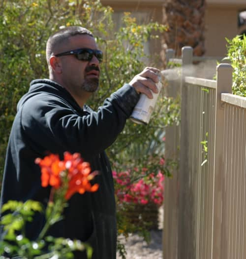 touching up iron fence with spray paint