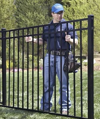 man installing section of iron fence