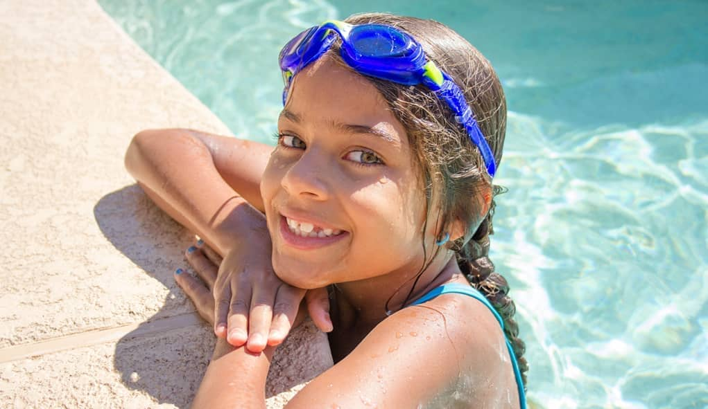 girl smiling while in swimming pool